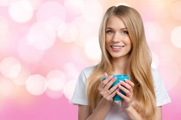 Jeune femme boit du café ou du thé Photo Premium