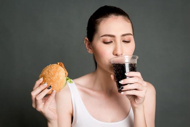 Jeune femme boit du cola et tenant un hamburger sur fond gris. concept de restauration rapide et de malbouffe Photo Premium