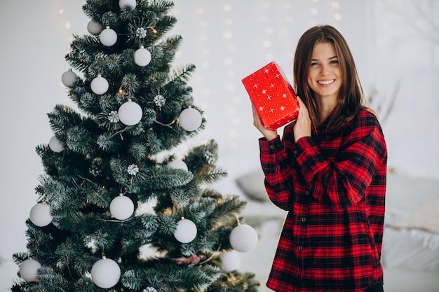 Jeune Femme Avec Boîte-cadeau Par L'arbre De Noël Photo gratuit