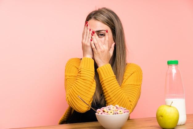 Jeune femme avec bol de céréales couvrant les yeux et regardant à travers les doigts Photo Premium