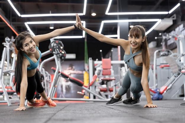 Jeune femme en bonne santé asiatique deux personnes push-up sur des poids et donnant haut cinq Photo Premium