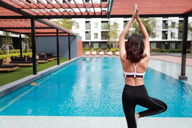 Jeune femme en bonne santé et sportive faire du yoga étirement en plein air Photo Premium