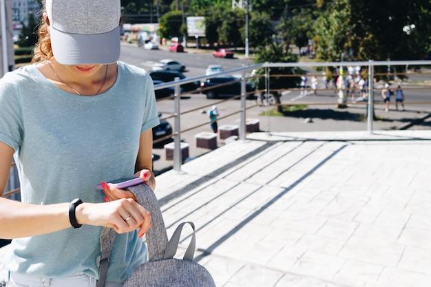 Jeune femme en bonnet et avec un sac à dos synchronise les données avec les montres intelligentes et le téléphone Photo Premium