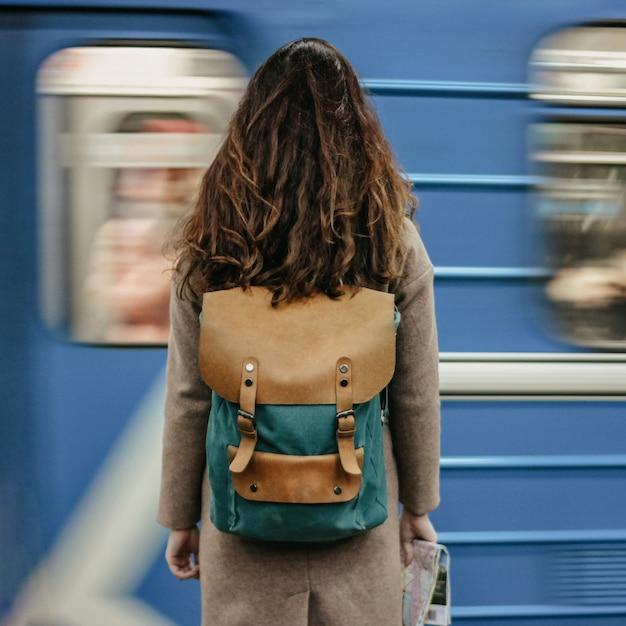 Jeune femme bouclée voyageuse tête rouge avec sac à dos et carte dans la station de métro en face du train Photo Premium