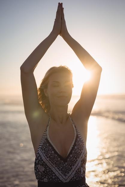 Jeune Femme, à, Bras Levés, Faire, Yoga, Plage Photo gratuit