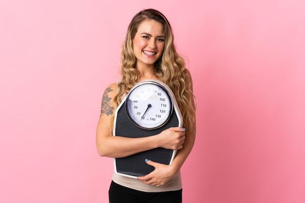 Jeune Femme Brésilienne Isolée Sur Rose Avec Peseuse Photo Premium