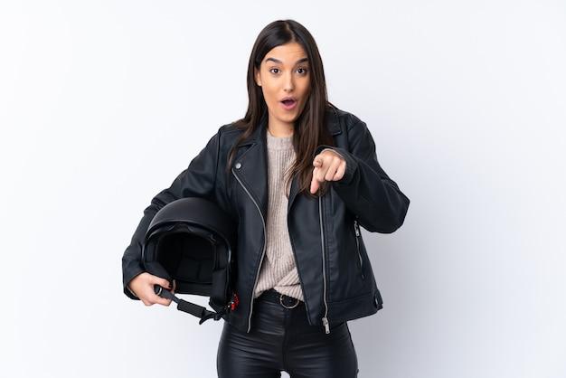 Jeune Femme Brune Avec Un Casque De Moto Sur Un Mur Blanc Isolé Surpris Et Pointant Vers L'avant Photo Premium