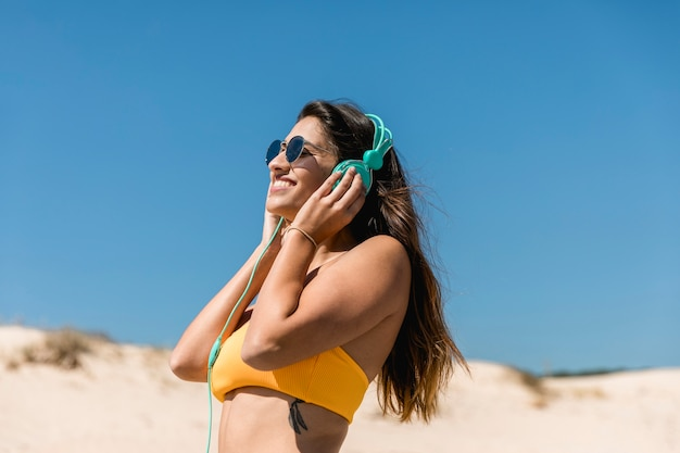 Jeune femme brune, écouter de la musique au casque Photo gratuit