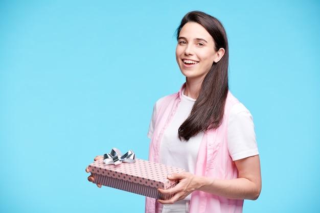 Jeune Femme Brune Excitée En Tenue Décontractée Tenant Une Boîte-cadeau Emballée Avec Un Arc Sur Le Dessus Tout En Vous Regardant Photo Premium