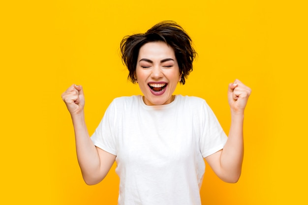 Jeune Femme Brune Heureuse Avec Une Coupe Courte Dans Un T-shirt Blanc Sur Fond Jaune. Portrait D'une Jeune Femme Avec Diverses émotions Sur Fond Jaune. Espace Pour Le Texte Photo Premium
