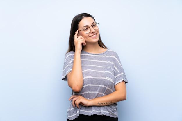 Jeune femme brune isolée bleue avec des lunettes Photo Premium