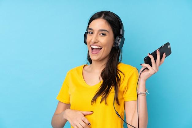 Jeune Femme Brune Sur Un Mur Bleu Isolé, écouter De La Musique Et Faire Un Geste De Guitare Photo Premium
