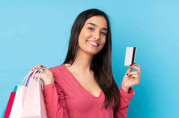 Jeune Femme Brune Sur Mur Bleu Isolé Tenant Des Sacs à Provisions Et Une Carte De Crédit Photo Premium