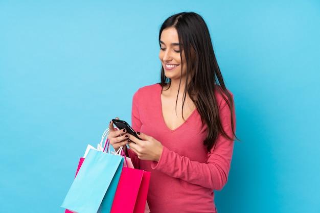 Jeune Femme Brune Sur Un Mur Bleu Isolé Tenant Des Sacs à Provisions Et écrivant Un Message Avec Son Téléphone Portable à Un Ami Photo Premium