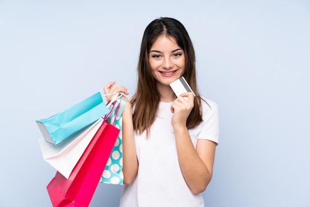 Jeune Femme Brune Sur Mur Bleu Tenant Des Sacs à Provisions Et Une Carte De Crédit Photo Premium