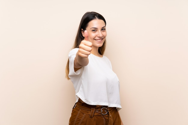 Jeune femme brune avec le pouce levé parce qu'il s'est passé quelque chose de bien Photo Premium