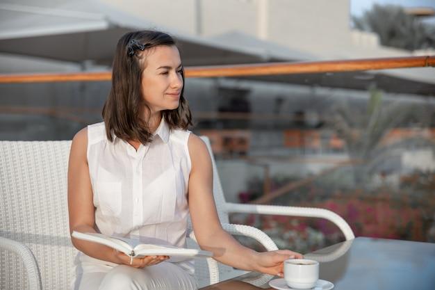 Jeune Femme Brune Profite De La Matinée Avec Une Tasse De Boisson Chaude Et Un Livre Dans Ses Mains. Photo gratuit