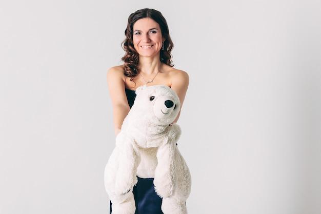 Jeune femme brune en robe de soirée avec jouet ours polaire Photo Premium