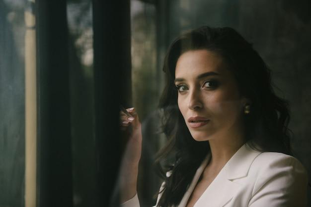 Jeune femme brune sexy en costume fumant une cigarette par la fenêtre à l'intérieur Photo Premium