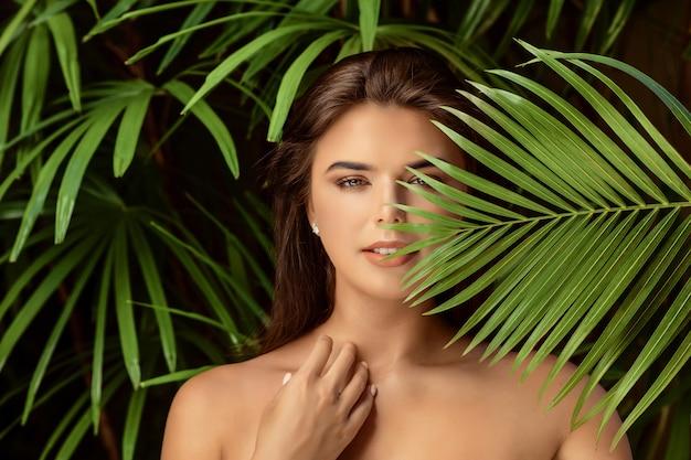 Jeune femme brune souriante avec grande feuille verte, concept de gens de soins spa bouchent Photo Premium