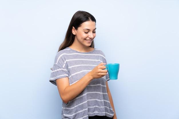 Jeune femme brune tenant une tasse de café Photo Premium