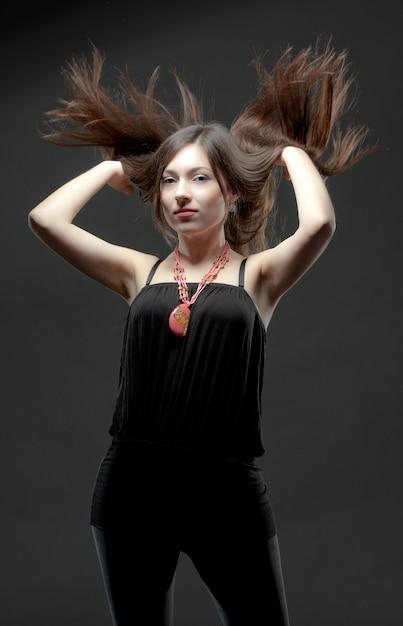 Jeune Femme Brune En Vêtements Décontractés Noirs Et Accessoires Massifs Debout Et Tournant La Tête Avec Le Vent Dans Ses Cheveux Sur Fond Gris En Studio Photo Photo Premium