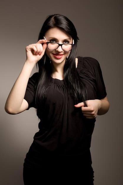 Jeune Femme Brune En Vêtements Noirs Et Lunettes à La Recherche Et Souriant Sur Fond Blanc En Studio Photo Photo Premium