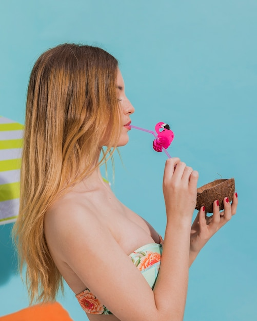 Jeune femme buvant une boisson tropicale en studio Photo gratuit