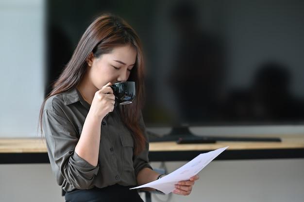 Jeune femme buvant du café et analyse financière papier. Photo Premium