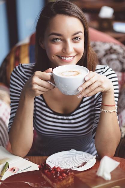 Jeune femme buvant du café au café urbain Photo gratuit