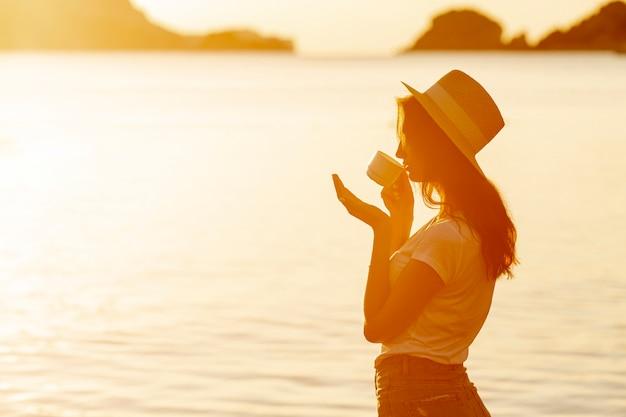 Jeune femme buvant du café au coucher du soleil Photo gratuit