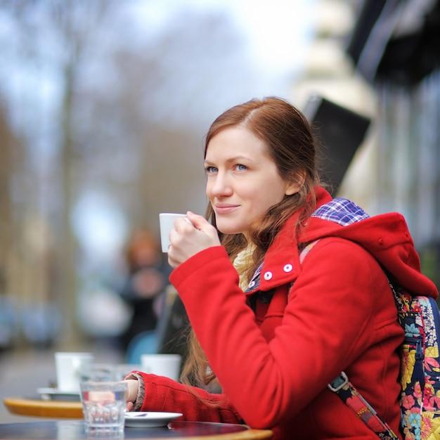 Jeune femme buvant du café dans un café de rue parisien Photo Premium