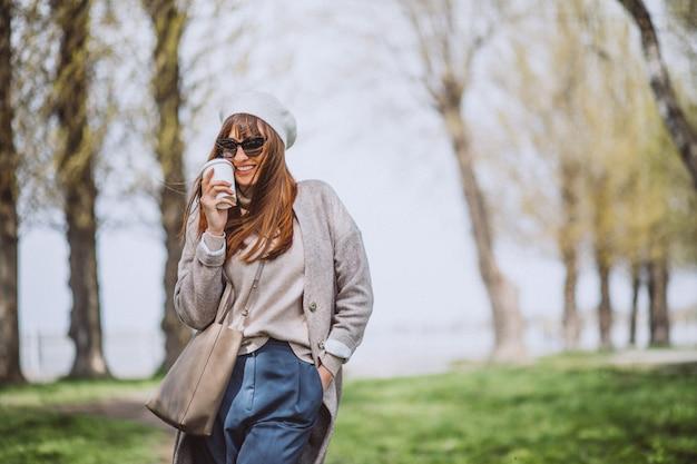Jeune femme buvant du café dans le parc Photo gratuit