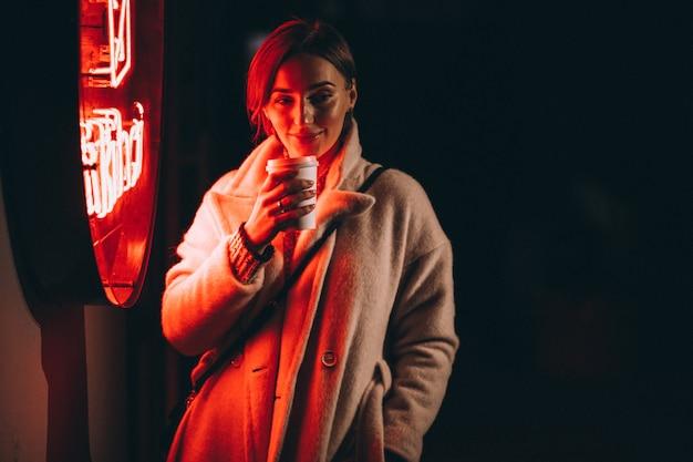 Jeune femme buvant du café dans la rue de nuit Photo gratuit