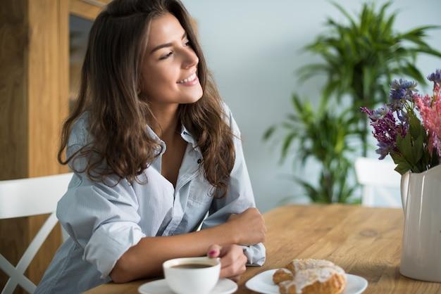 Jeune Femme Buvant Du Café Dans La Salle à Manger Photo gratuit