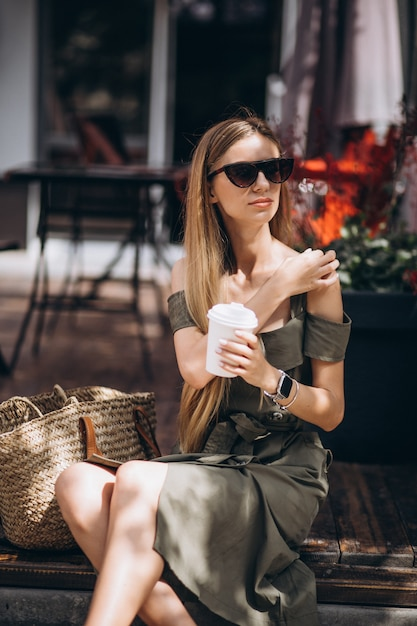 Jeune femme buvant du café devant le café Photo gratuit