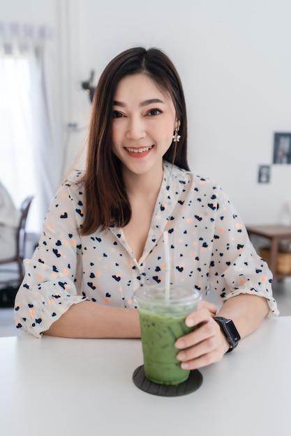 Jeune Femme Buvant Du Thé Vert Latte Dans Un Café Photo Premium