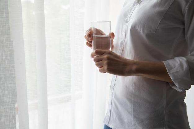Jeune femme buvant de l'eau minérale sur le rideau blanc windows texture fond. Photo Premium