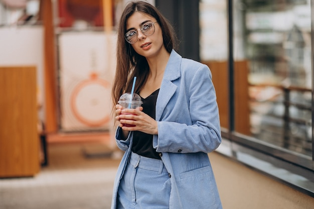 Jeune Femme Buvant Un Verre De Glace à L'extérieur De La Rue Photo gratuit