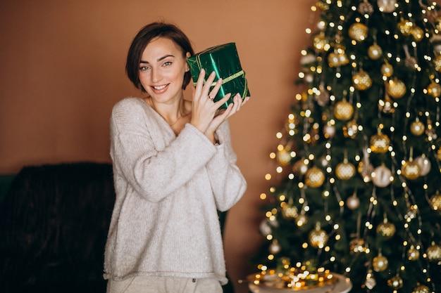 Jeune femme avec un cadeau de noël près du sapin de noël Photo gratuit