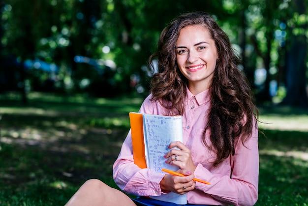 Jeune femme avec carnet de notes dans le parc Photo gratuit