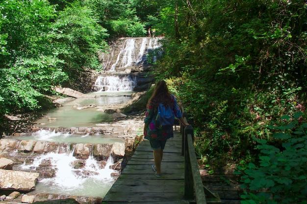 Jeune femme sur une cascade avec sac à dos de retour à la caméra Photo Premium