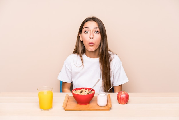 Jeune Femme Caucasienne Ayant Un Petit Déjeuner Isolé Hausse Les épaules Et Les Yeux Ouverts Confus. Photo Premium
