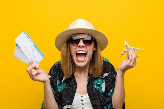 Jeune femme caucasienne détenant des billets d'avion très heureux. Photo Premium