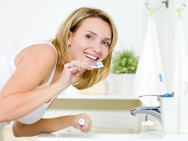 Jeune Femme Caucasienne Heureuse, Nettoyer Les Dents Avec Une Brosse à Dents Dans La Salle De Bains Photo gratuit