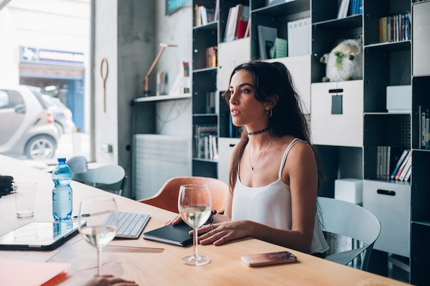 Jeune femme caucasienne en interaction et assis dans le bureau de co-working moderne Photo Premium