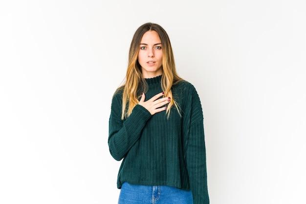 Jeune Femme Caucasienne Isolée Sur Un Espace Blanc En Prêtant Serment, Mettant La Main Sur La Poitrine. Photo Premium