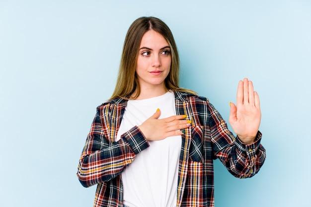 Jeune Femme Caucasienne Isolée Sur L'espace Bleu En Prêtant Serment, Mettant La Main Sur La Poitrine. Photo Premium