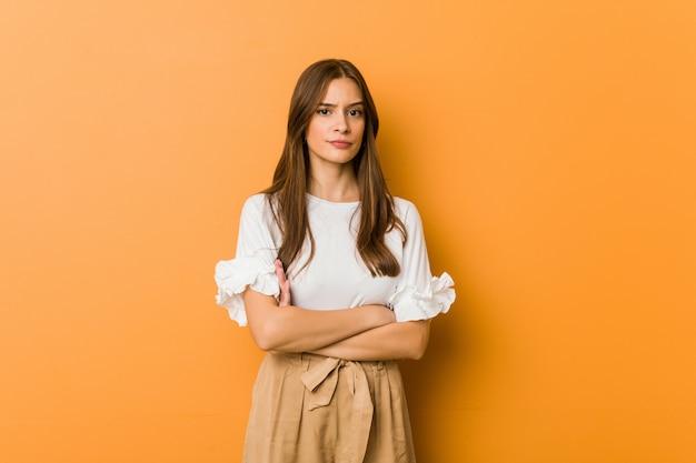 Jeune femme caucasienne malheureuse à la recherche à huis clos avec une expression sarcastique. Photo Premium