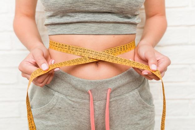 Jeune femme caucasienne mesurant sa taille Photo Premium